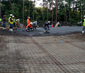 Concrete with reinforcing mesh on top of compacted gravel on top of geotech fabric